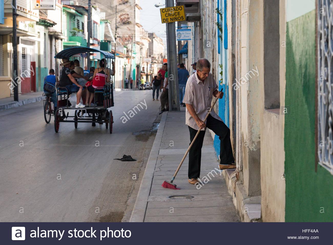 Der tur  Kubaner Lebensstil: Greis fegen der Tür eines Gebäudes. Auf der ...