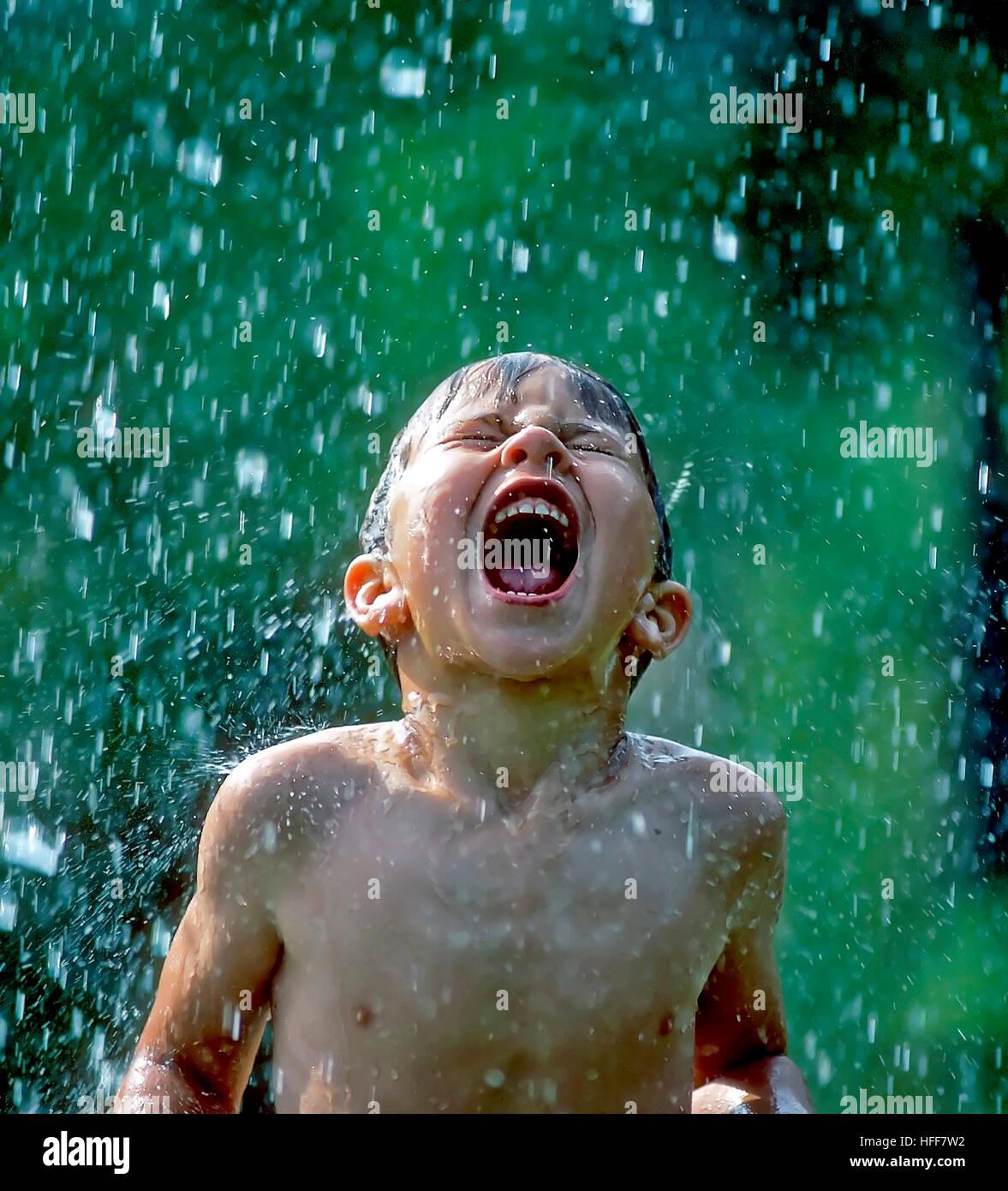 Ein kleiner Junge fängt Regentropfen in den offenen Mund mit einem Ausdruck von purer Lebensfreude und jugendlichem Stockbild