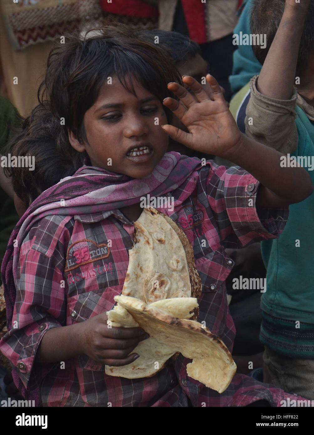 Pakistanische Arme Menschen halten trockenes Brot, wie sie gegen ...