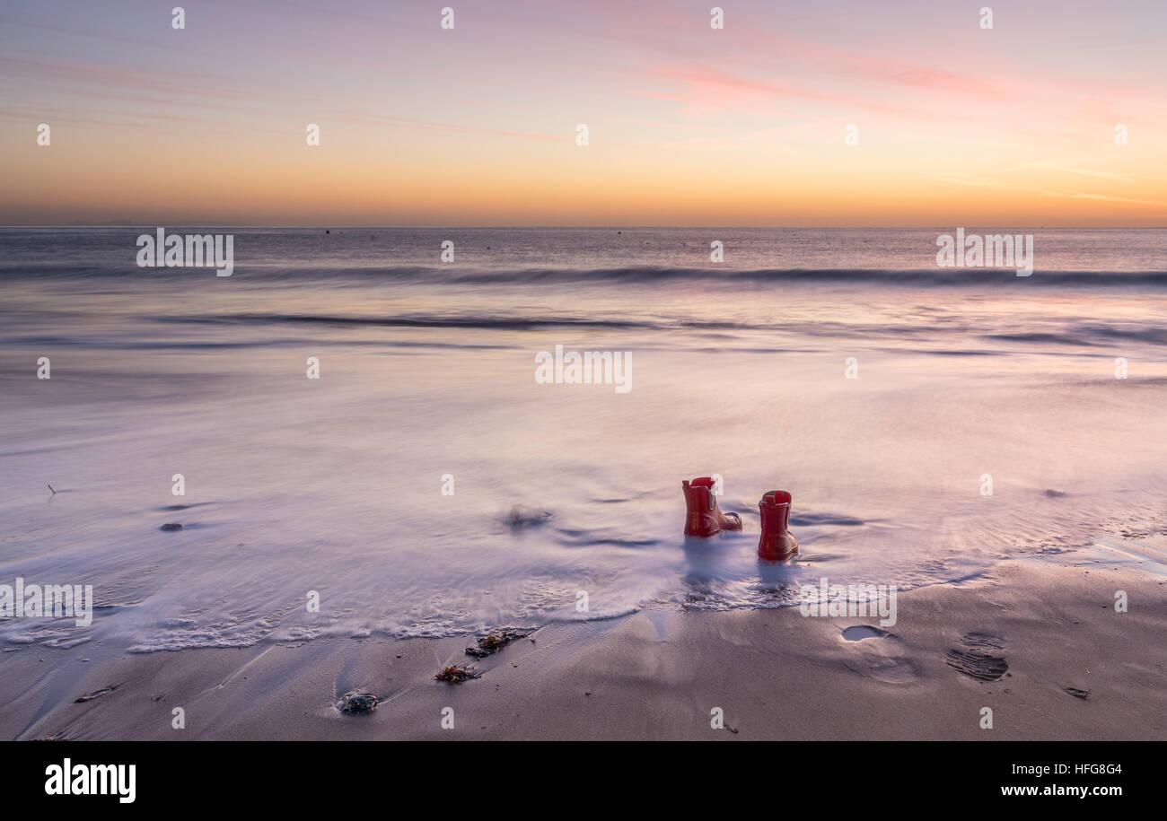 hinterlassen ihre Stiefel in der Bucht bei Sonnenaufgang Stockbild