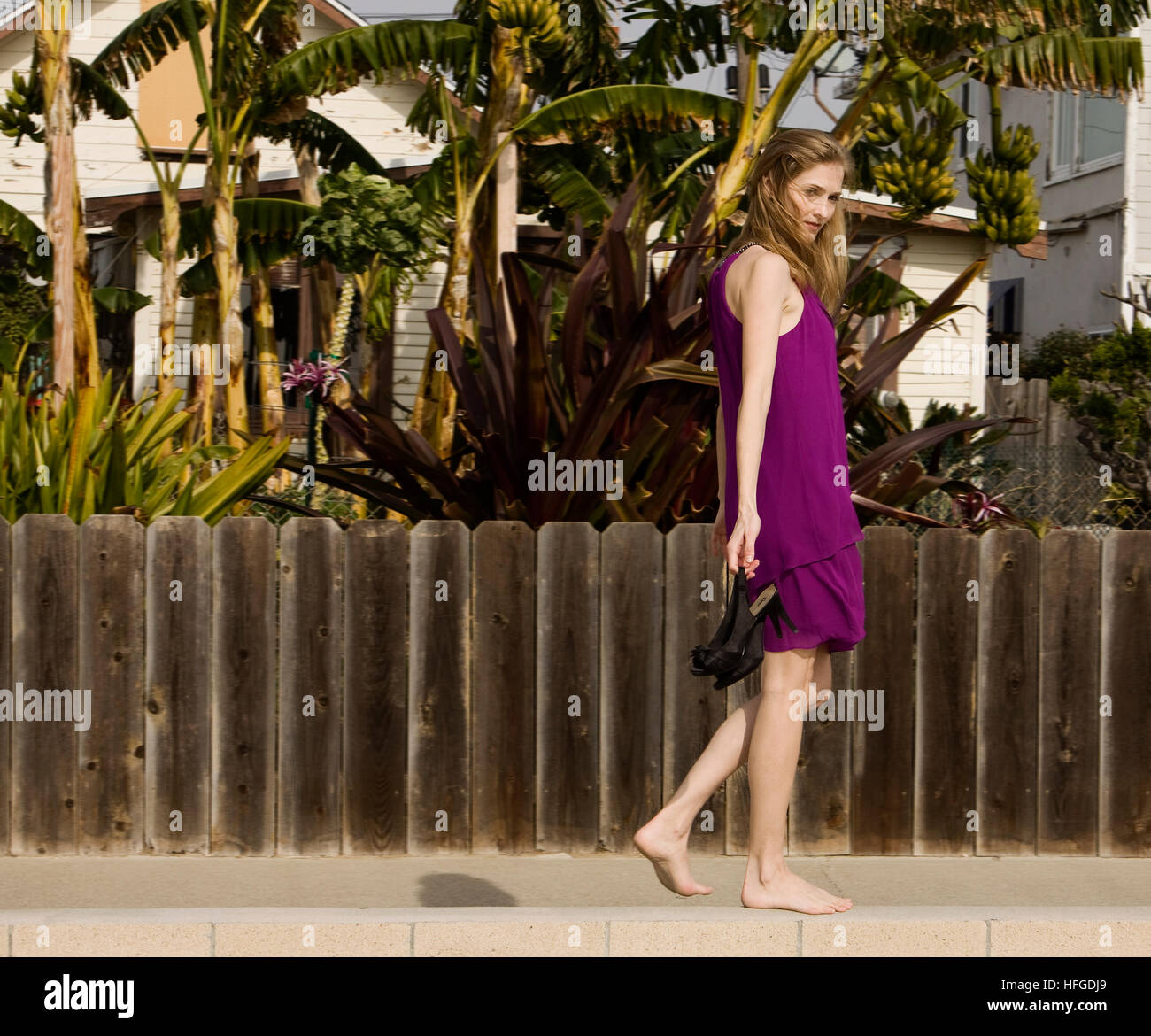 Frau zu Fuß entlang einer Wand in ein Cocktail-Kleid tragen ihre ...