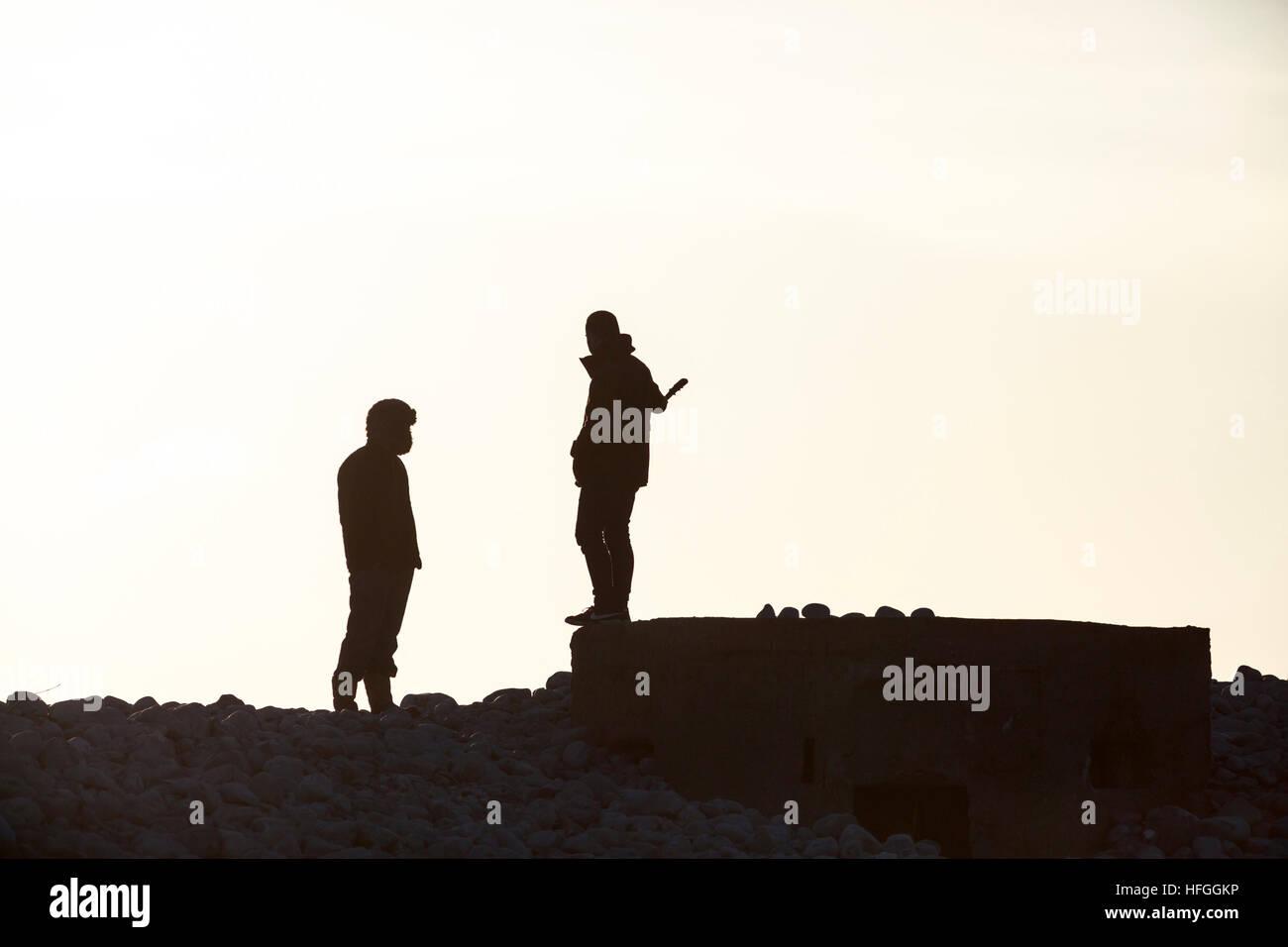 Silhouette von zwei Jugendlichen bedroht Stockbild