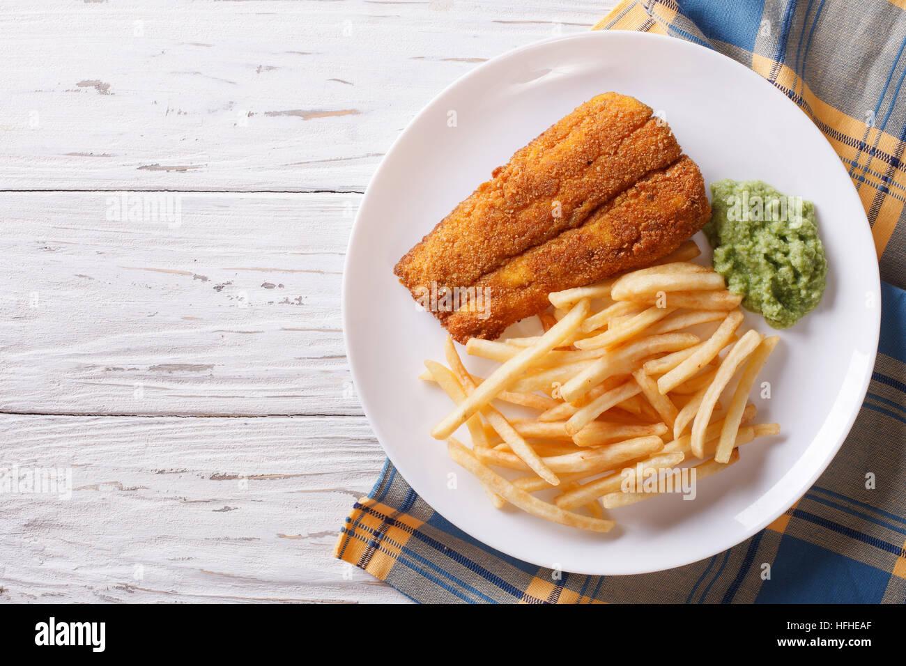 englisch essen gebratener fisch in teig mit pommes frites und erbsen p ree auf den teller. Black Bedroom Furniture Sets. Home Design Ideas