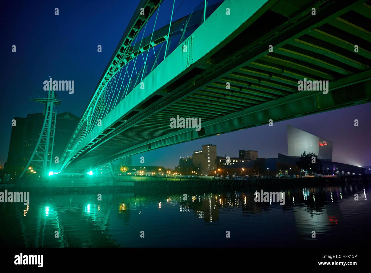 Manchester Salford Quays Mediacity Liebe MediaCityUK Millennium Brücke grünes Licht am Abend Nacht Dämmerung Stockbild