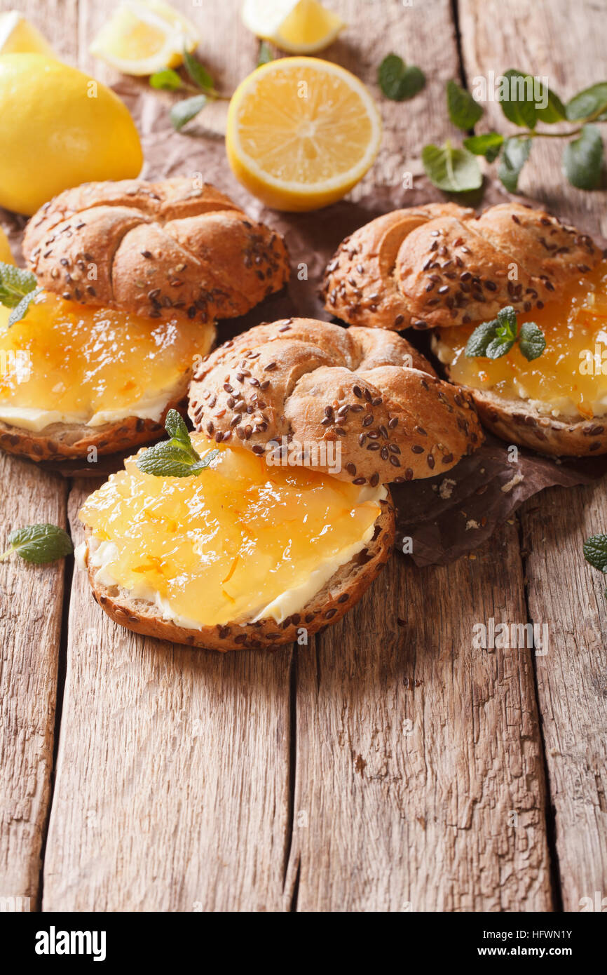 Süße Brötchen mit Marmelade und Butter Nahaufnahme Zitrone auf dem Tisch. vertikale Stockfoto