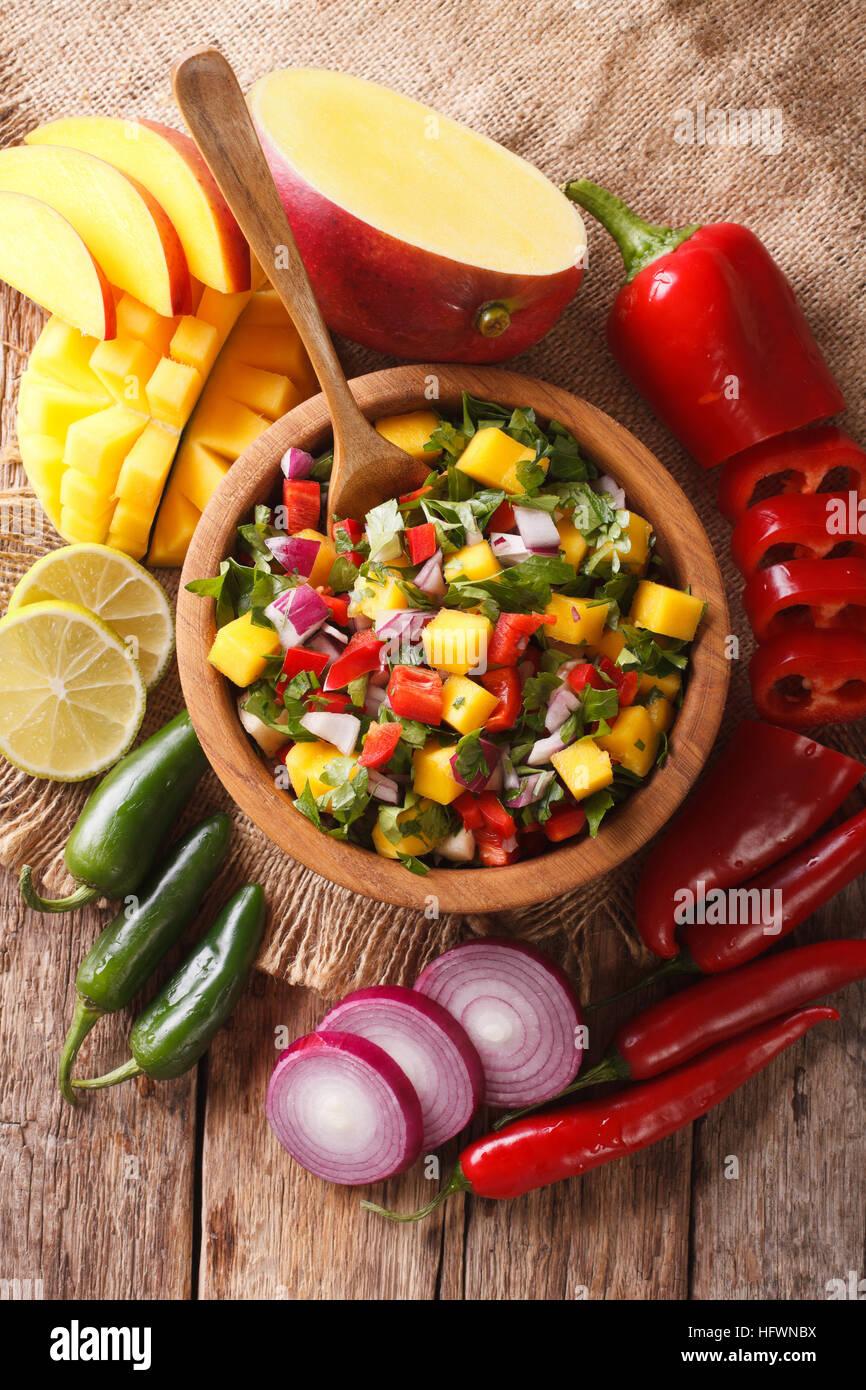 Salsa mit Mango, Koriander, Zwiebeln und Paprika in eine Schüssel geben und die Zutaten auf dem Tisch hautnah. Stockbild