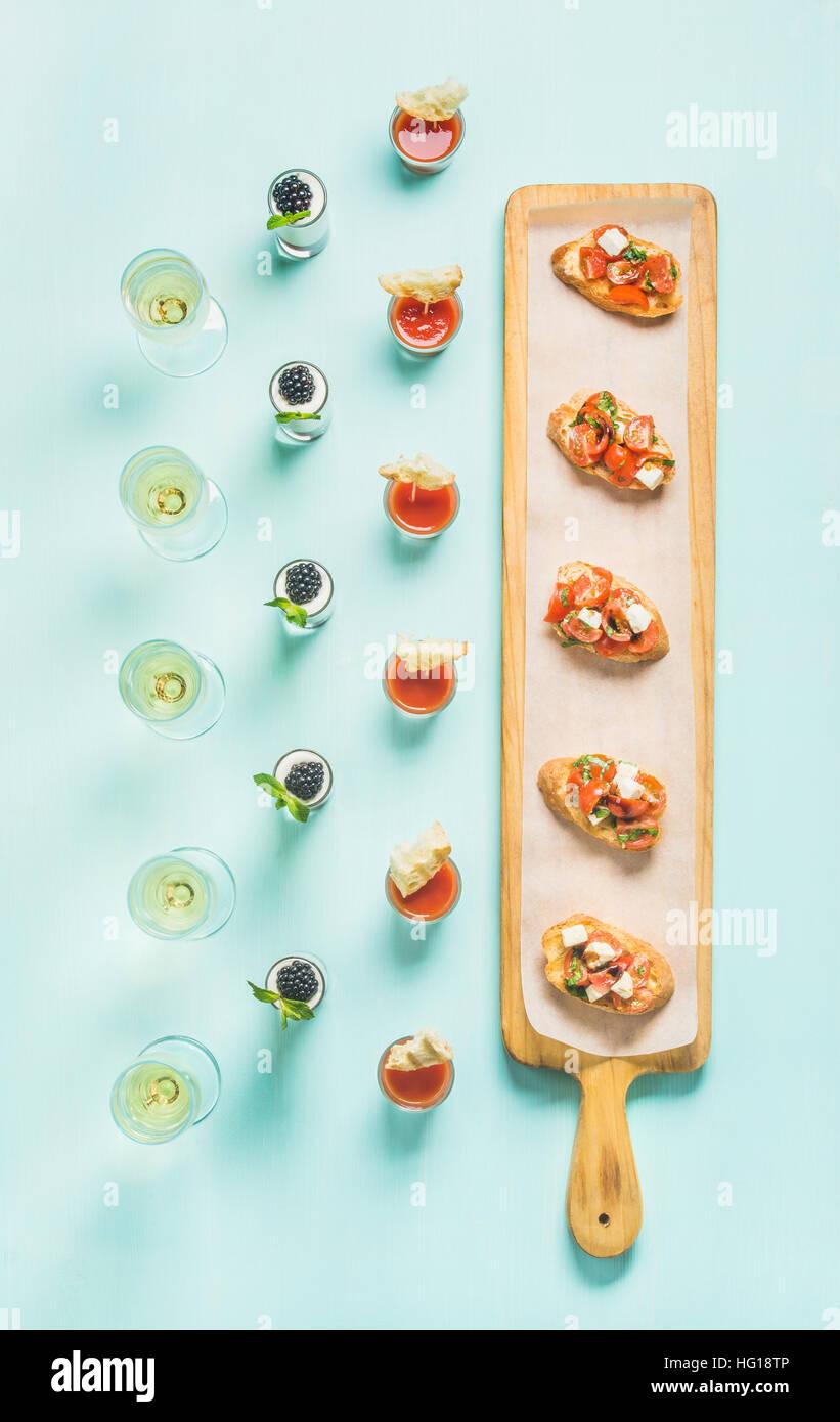Brushettas, Gazpacho Aufnahmen, Desserts, Snacks, Champagner über Pastellblau Hintergrund Stockbild