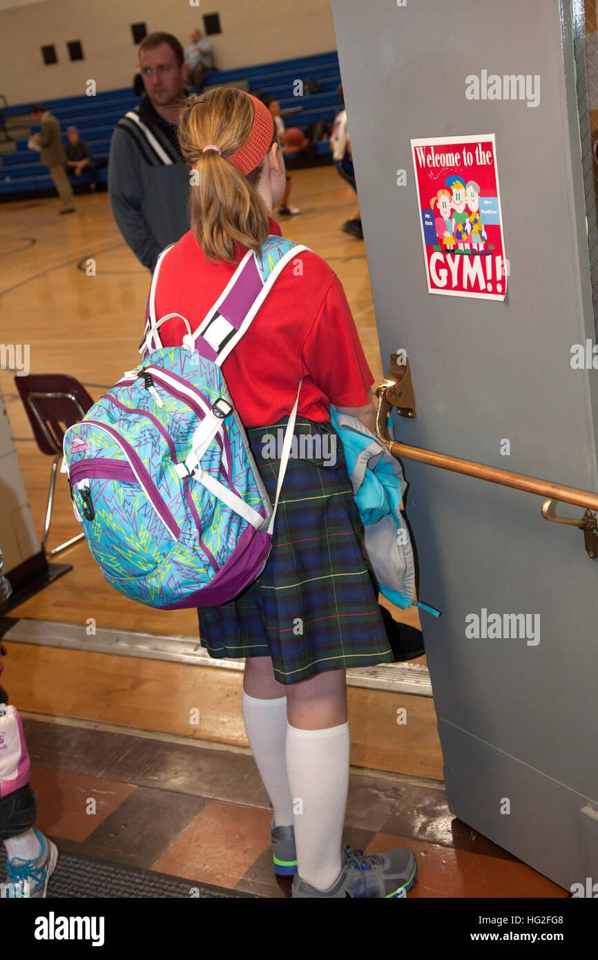 Junge Teen Girl mit Rucksack heimlich beobachten Jungen spielen Basketball in der Turnhalle. St Paul Minnesota MN Stockbild