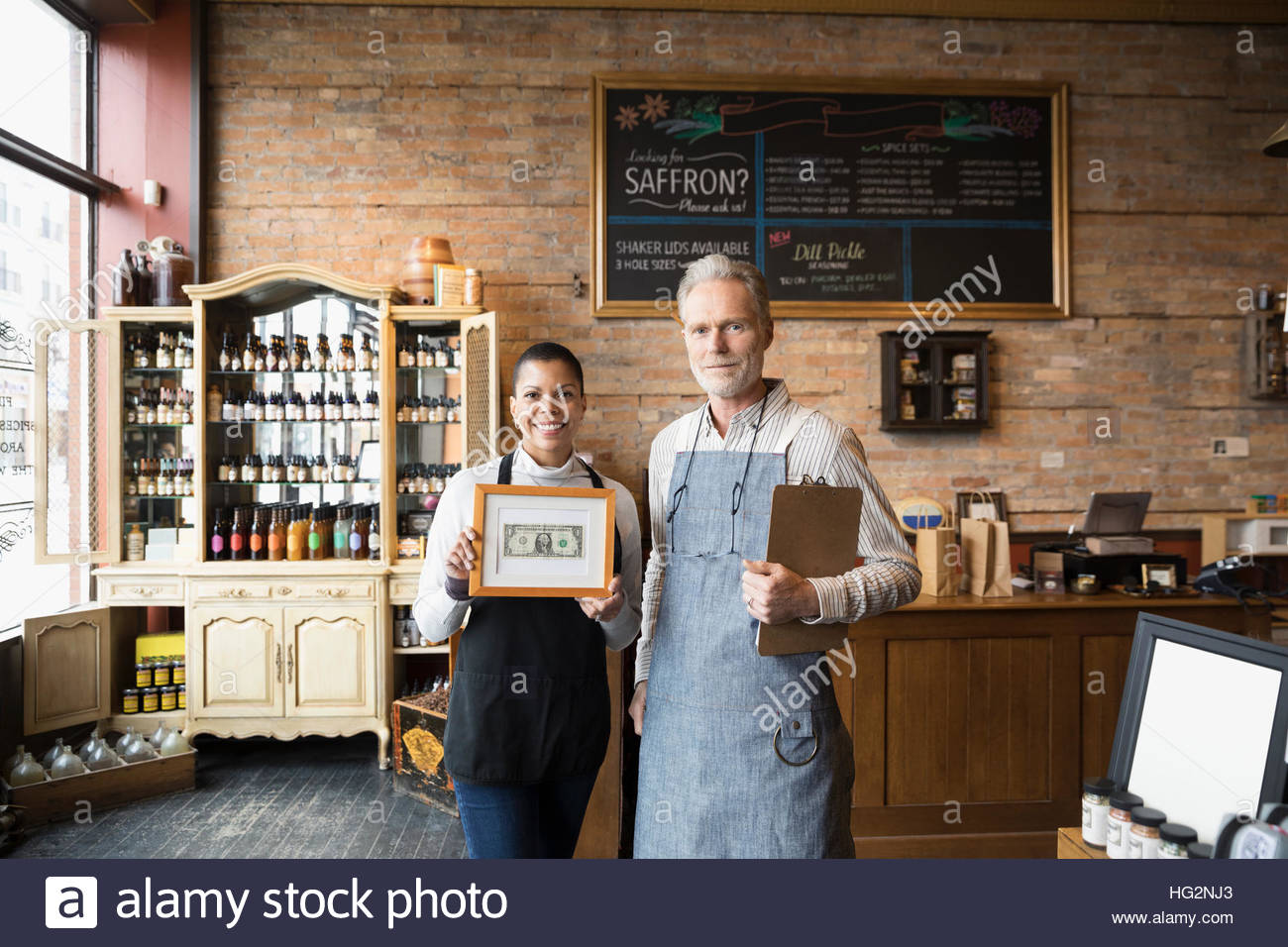 Porträt zuversichtlich Gewürz-Shop-Besitzer halten gerahmte ersten Dollar bill Stockbild