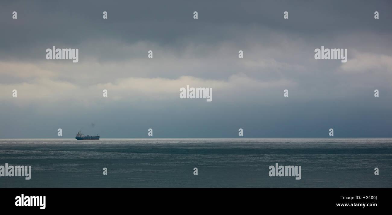 Graue trübe Seelandschaft mit einem Schiff am Horizont in der Nähe von Formia an der Mittelmeerküste Stockbild