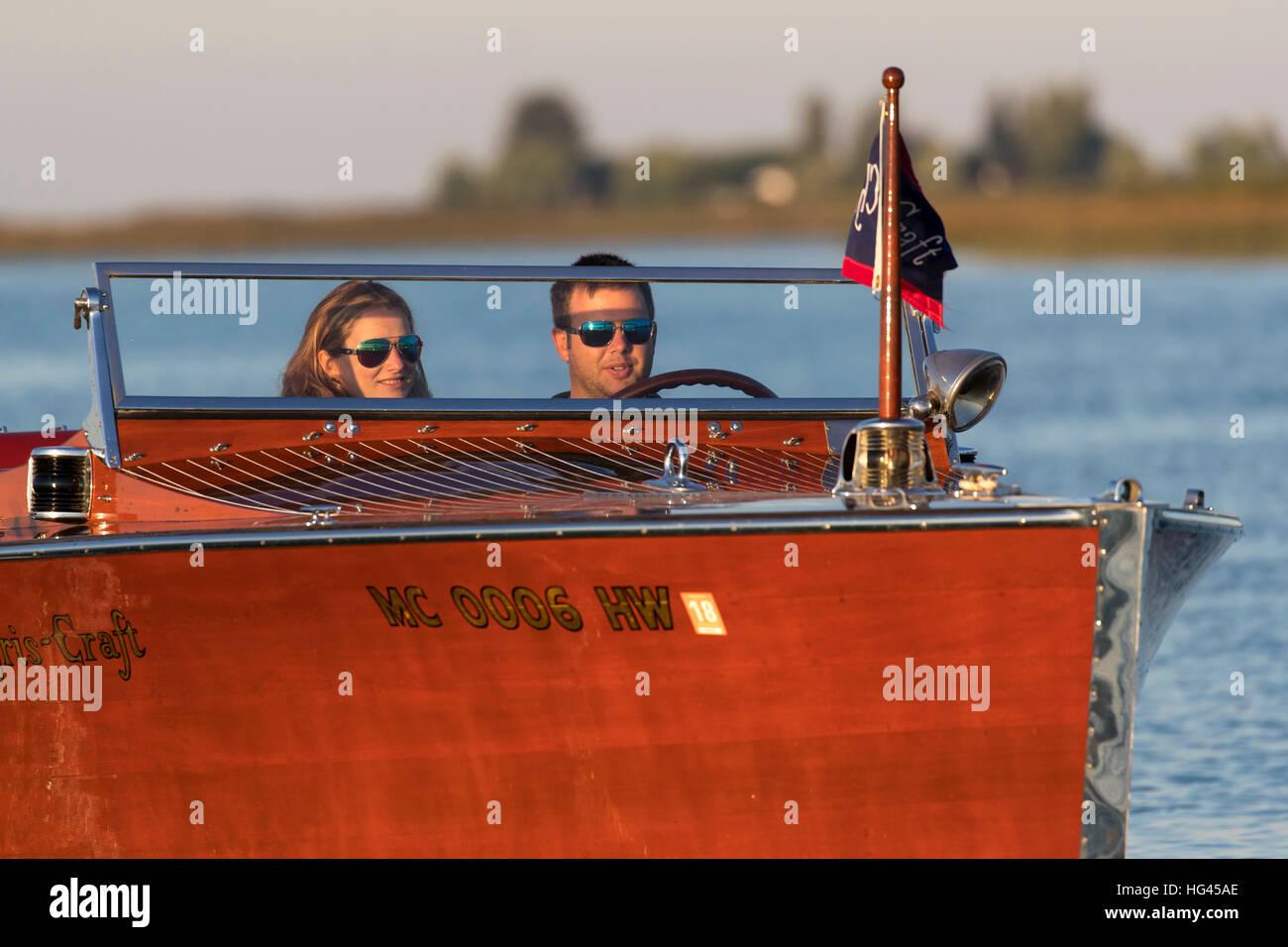 Ein junges Paar, eine antike, Holz Boot fahren. Stockbild