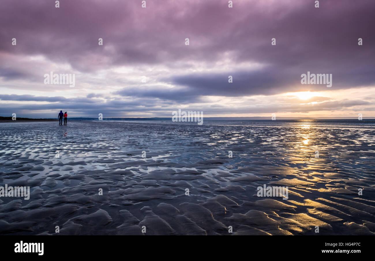 Ein paar walking am Strand am Abend Stockbild