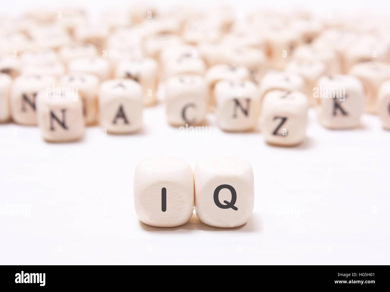 """Das Wort """"IQ"""" auf dem weißen Würfel auf einem Hintergrund von unscharfen Buchstaben. Das Konzept Stockbild"""