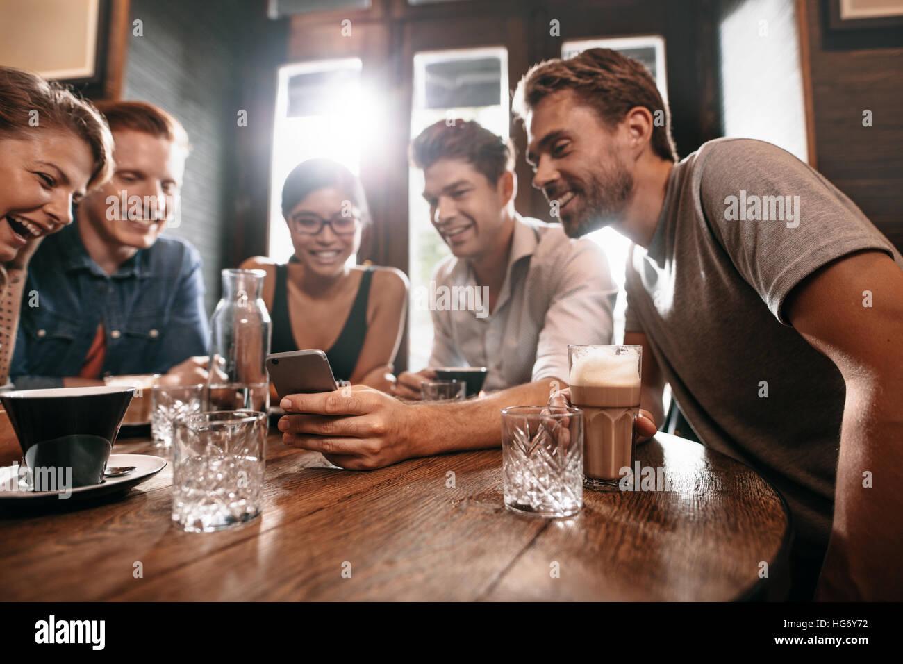 Gruppe von Freunden an einem Cafétisch sitzen und mit Blick auf Handy. Junge Männer und Frauen betrachten Stockbild