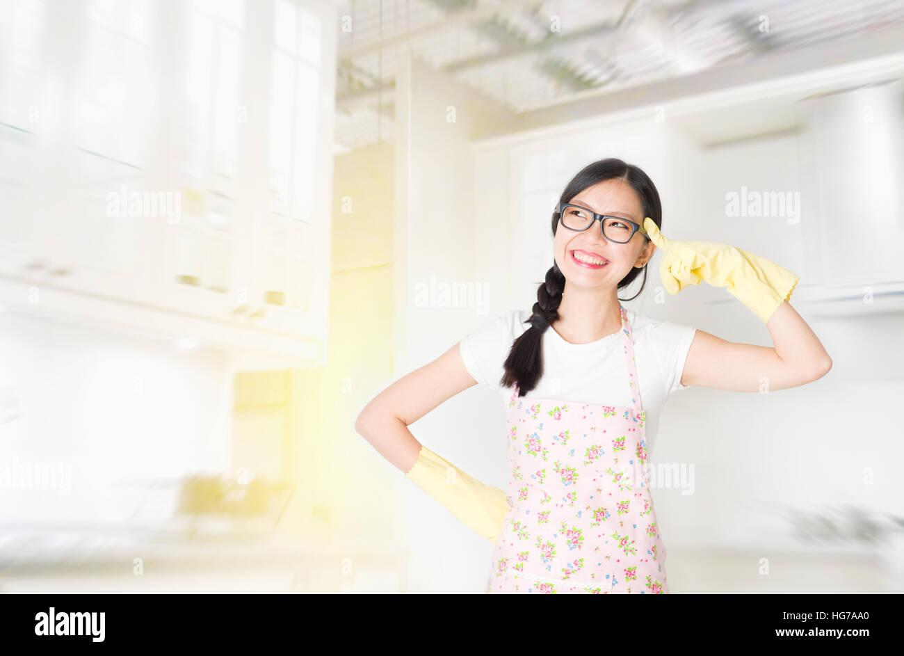 Junge asiatische Hausfrau beim Putzen der Küche zu denken Stockfoto ...