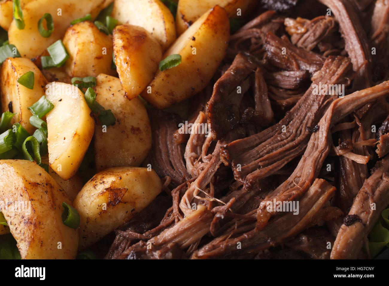 Leckere gezogener Schweinefleisch mit Bratkartoffeln Makro. horizontale Hintergrund Stockbild