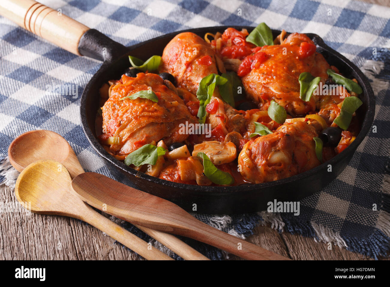 Italienische Küche: Huhn Cacciatori mit Pilzen hautnah in einer Pfanne erhitzen. Horizontale Stockbild