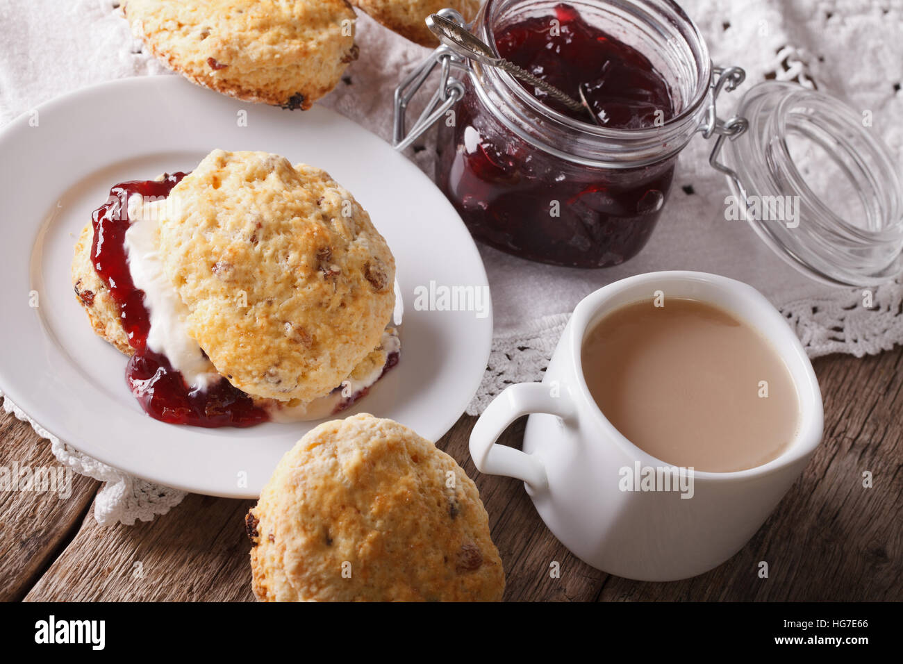Hausgemachte Scones mit Marmelade und Tee mit Milch Nahaufnahme auf dem Tisch. horizontale Stockbild