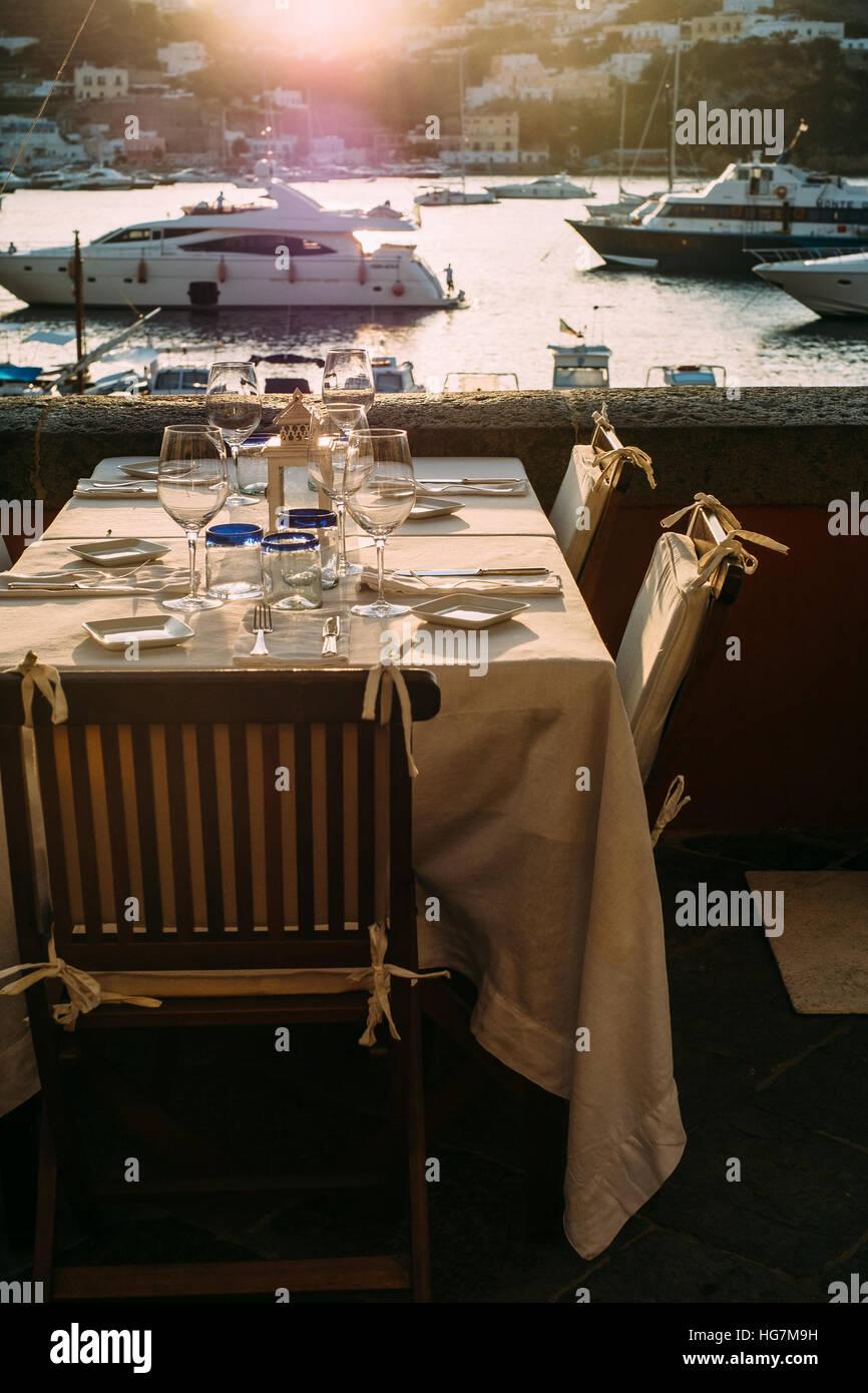 Ein Restaurant mit Blick auf den Hafen und den angedockten Yachten auf der Insel Ponza, Italien. Stockbild