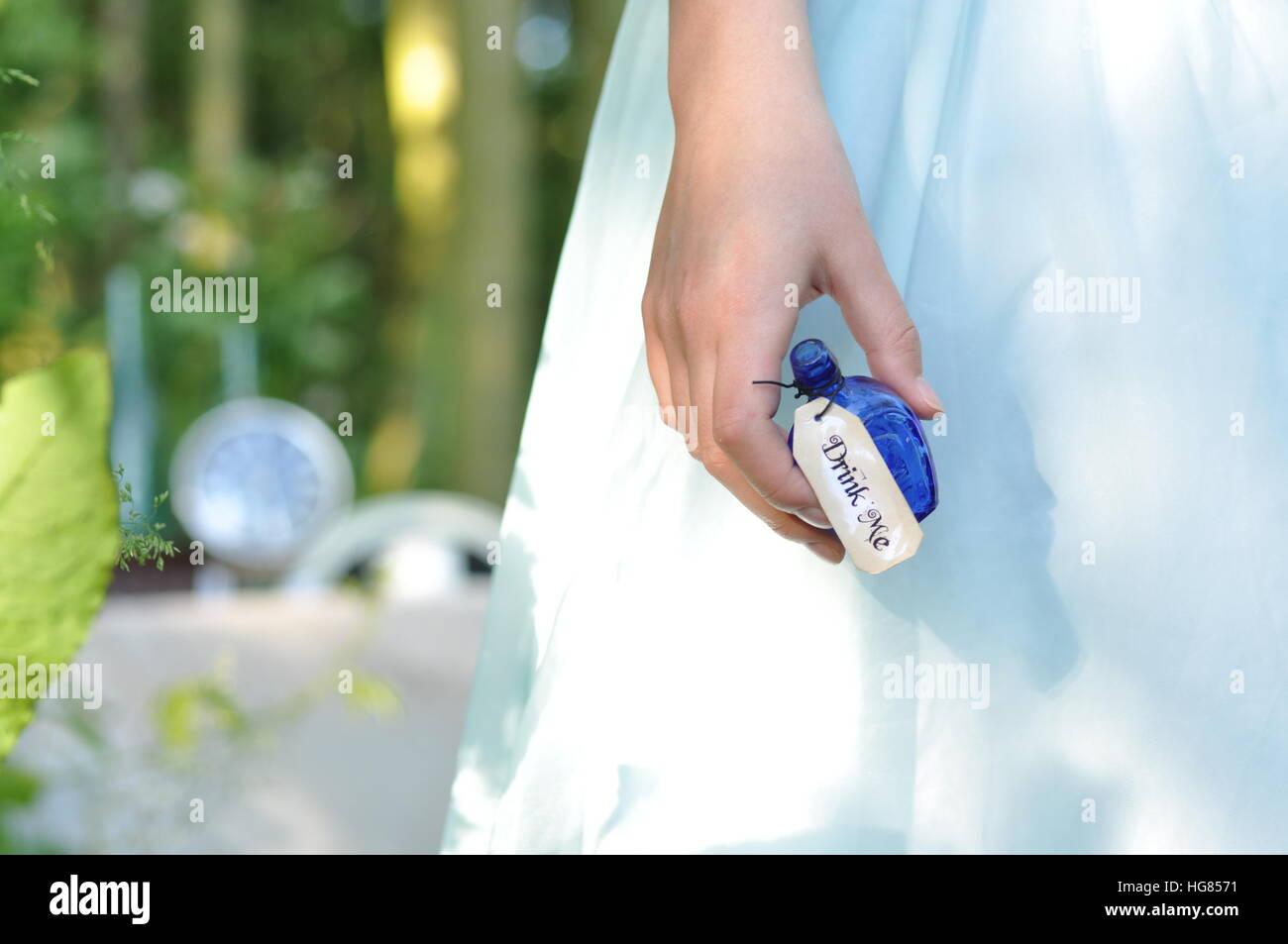 Trink mich. Alice im Wunderland. Mädchen im blauen Kleid Stockbild