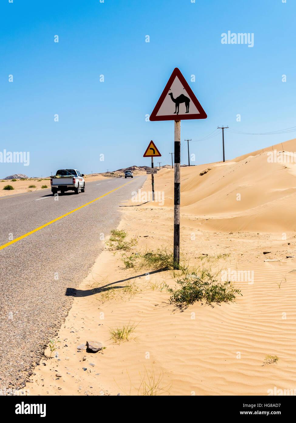 Straße durch Sandwüste mit Schild Warnung von Kamel Kreuzungen, Ash Sharqiyah Süd, Oman Stockbild