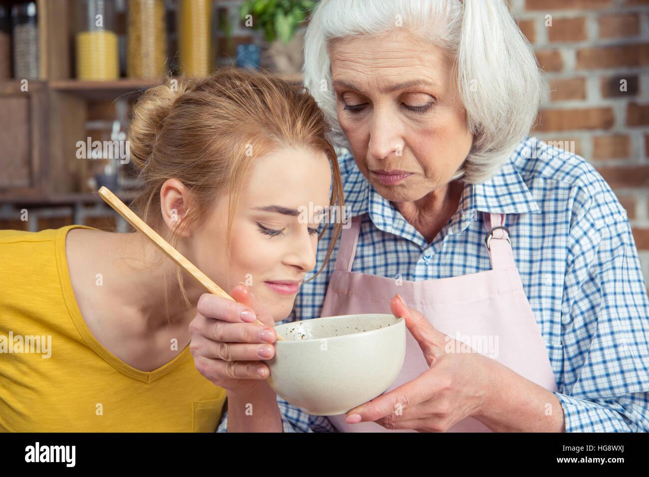 Enkelin und Großmutter zusammen zu kochen und auf der Suche in Schüssel Stockbild