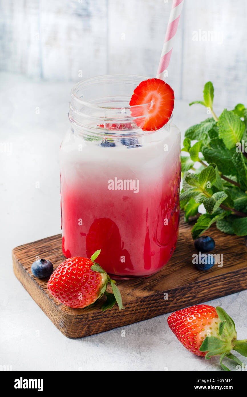 Erdbeer Smoothie in Glas mit cocktail Rohr für Trinkwasser. Kalter Sommer Erfrischungsgetränk Stockbild