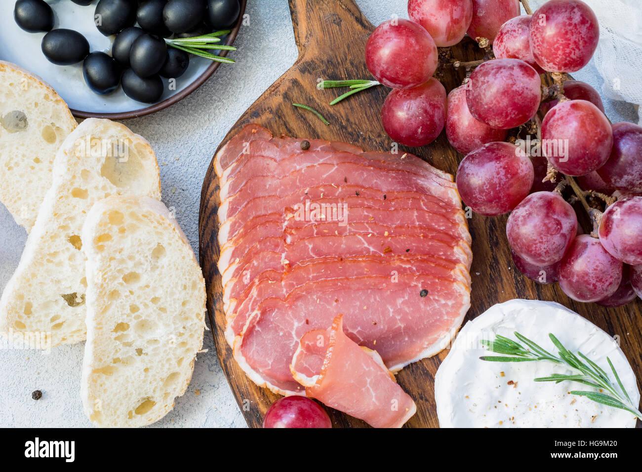 Wurstwaren, frisches Baguette, Trauben, Käse und schwarzen Oliven. Italienische Antipasti festgelegt. Nahaufnahme Stockfoto