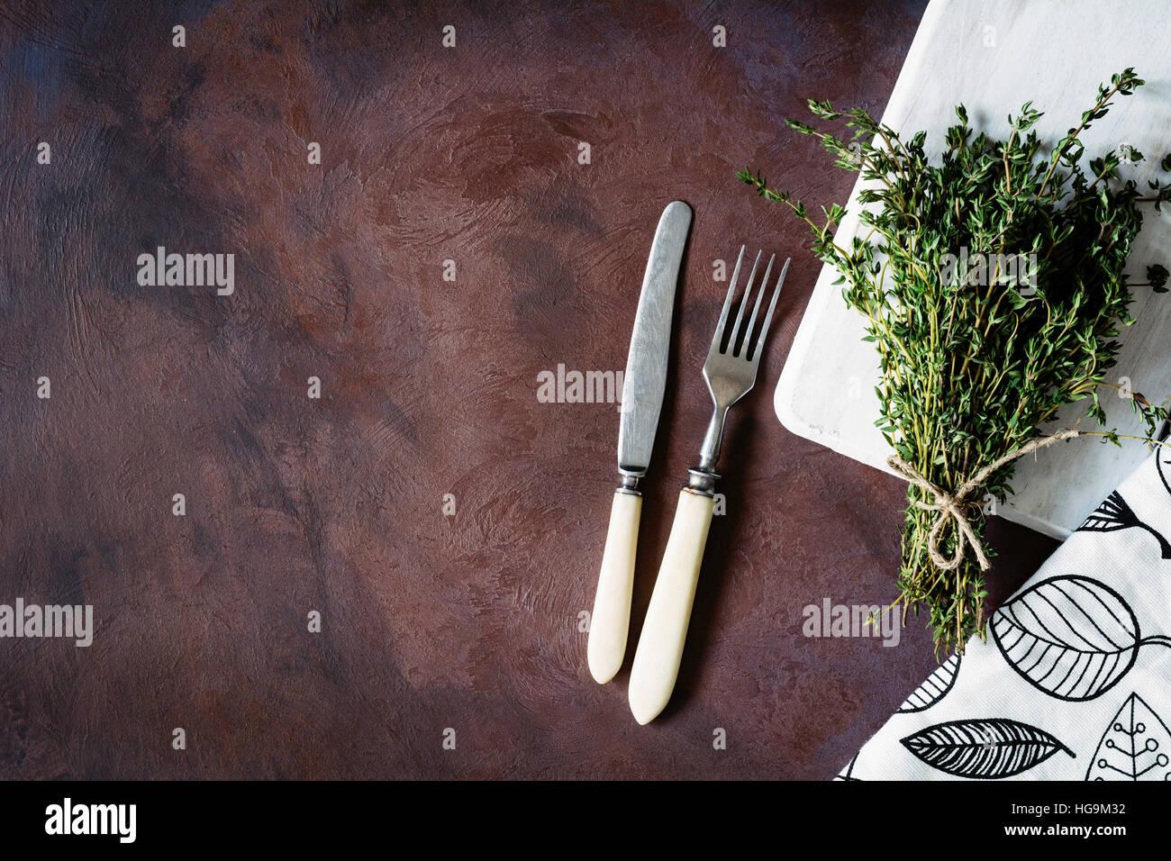 Vintage Besteck mit Elfenbein Griff, dunkle Textilien, Holzbrett und Bund frischen Thymian auf dunklem Hintergrund Stockbild