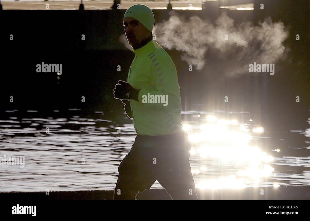 Kiel, Deutschland. 6. Januar 2017. Ein Jogger läuft entlang des Flusses Foerde kurz nach Sonnenaufgang in Kiel, Stockbild
