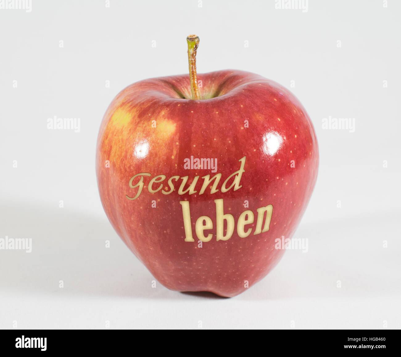 1 frische rote Apfel mit den Worten - lebe gesund - in deutscher Sprache auf einem weißen Hintergrund Stockbild