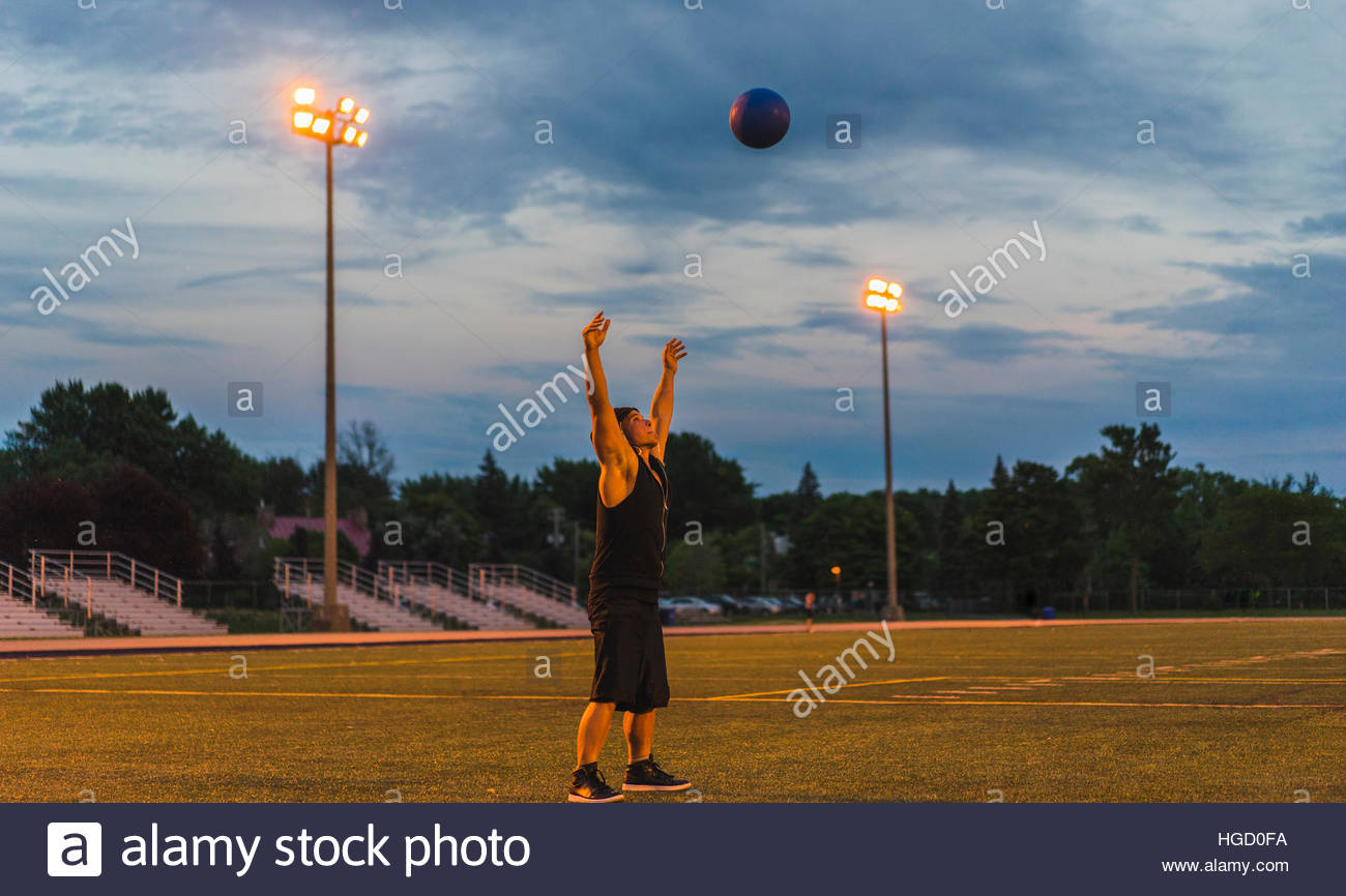 Athletischer Mann mit medizinball während der Arbeit in der Nacht, Montreal, Quebec, Kanada Stockbild
