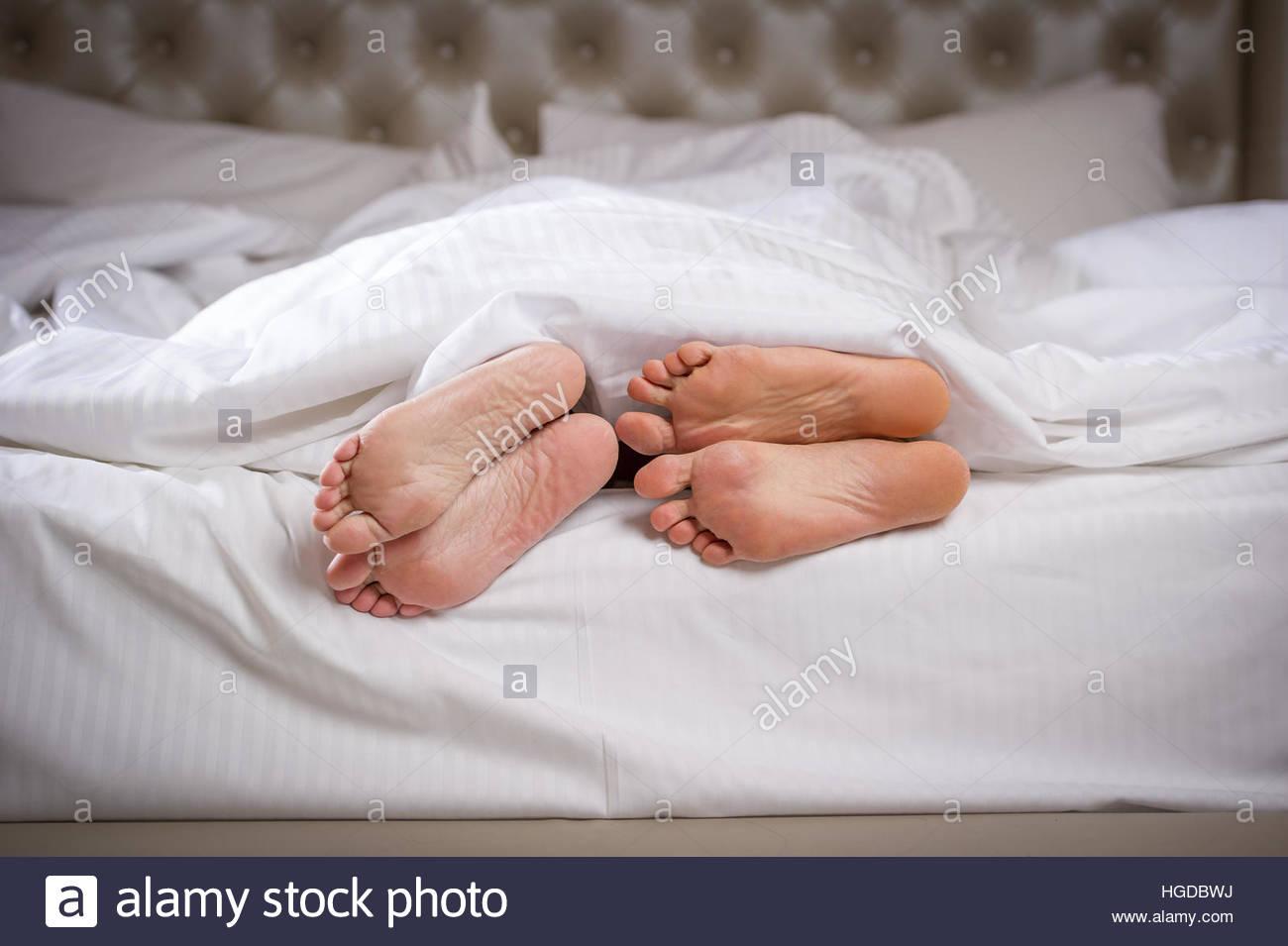 mann und frau die f e im bett unter der decke ragen als ob l ffel oder kuscheln stockfoto. Black Bedroom Furniture Sets. Home Design Ideas