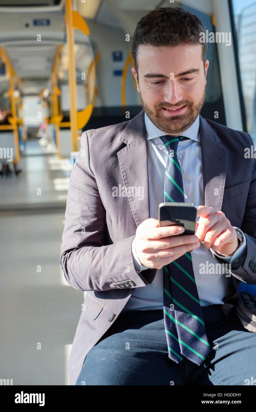 Geschäftsmann sucht auf seinem Mobiltelefon Weile geht zur Arbeit Stockbild