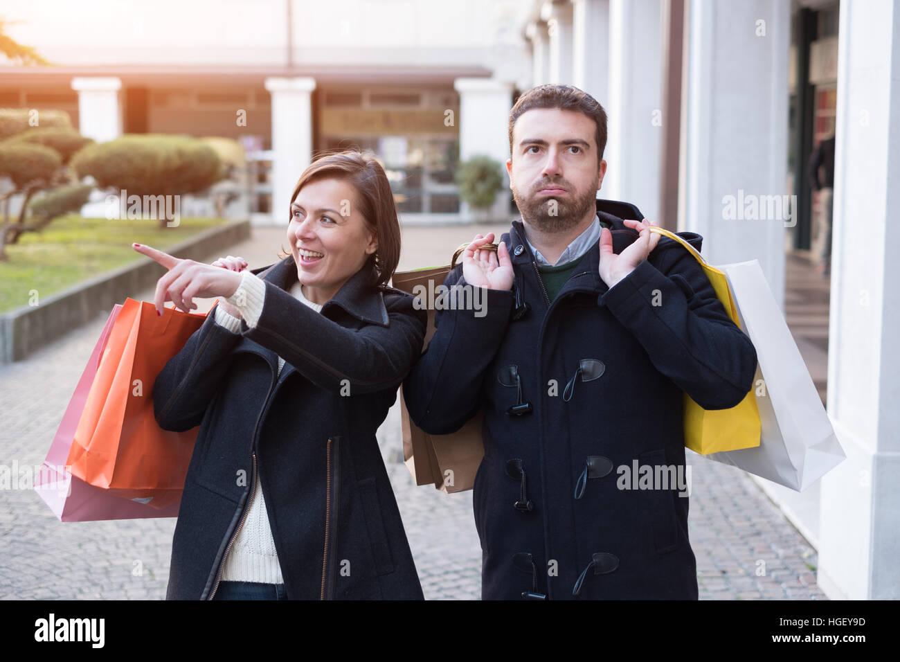 Mann sehr gelangweilt von der Kaufsucht seiner Freundin Stockfoto