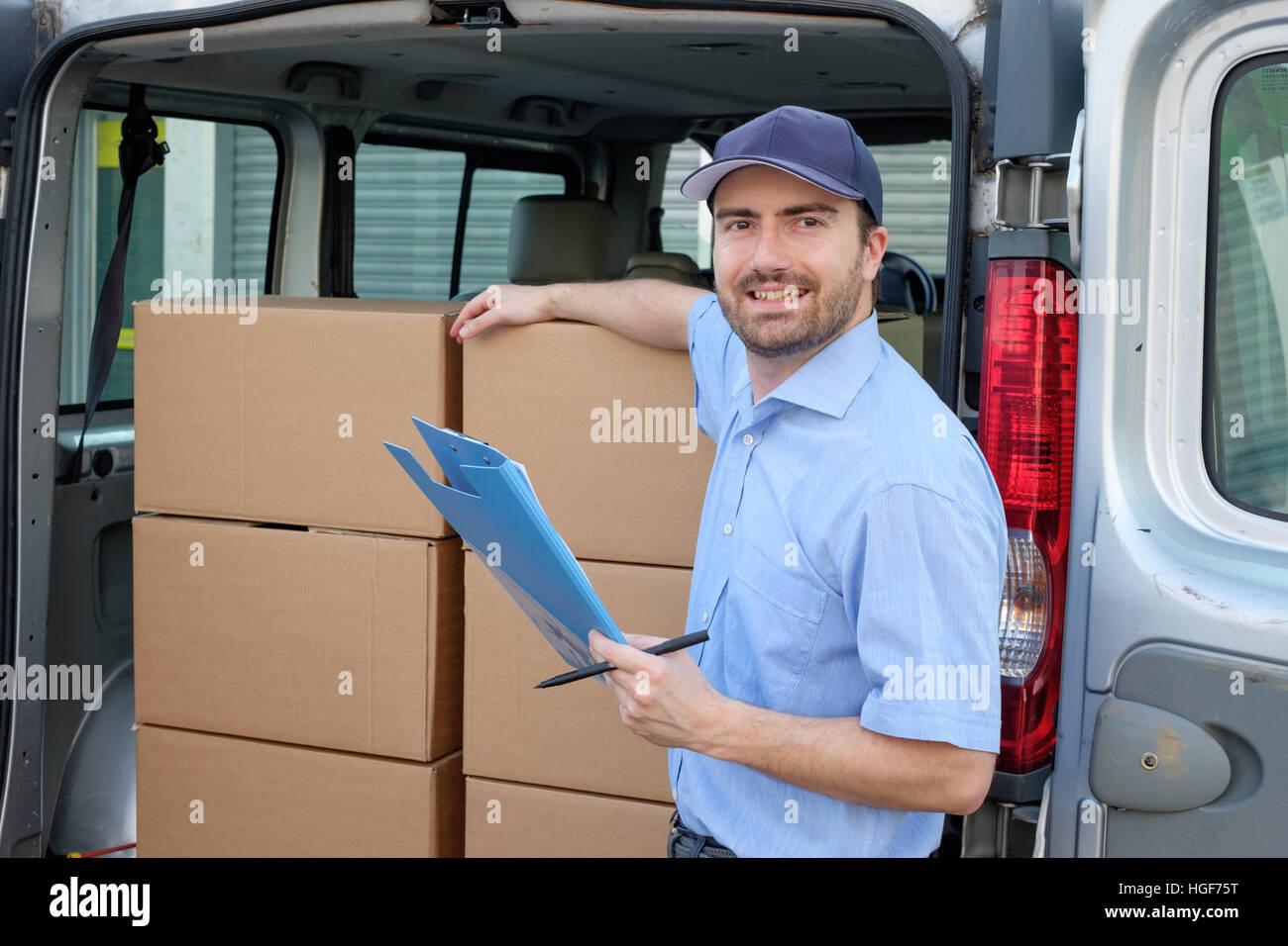 Porträt von Vertrauen Kurierdienst neben seinem Lieferwagen Stockbild