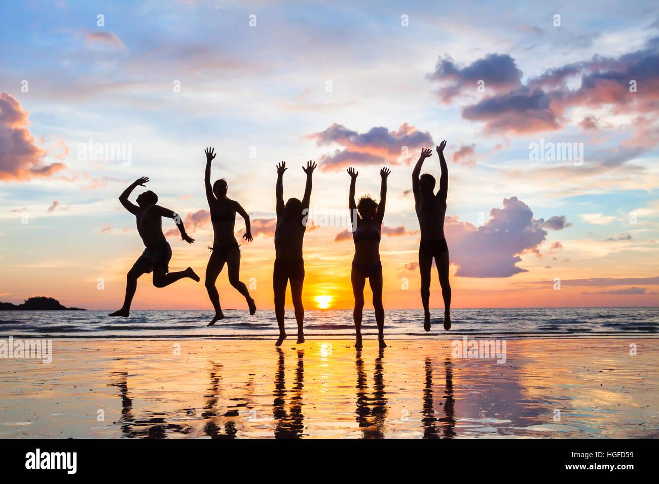 Gruppe von Menschen, die im Urlaub am Strand bei Sonnenuntergang, Silhouetten der happy Friends springen Stockbild