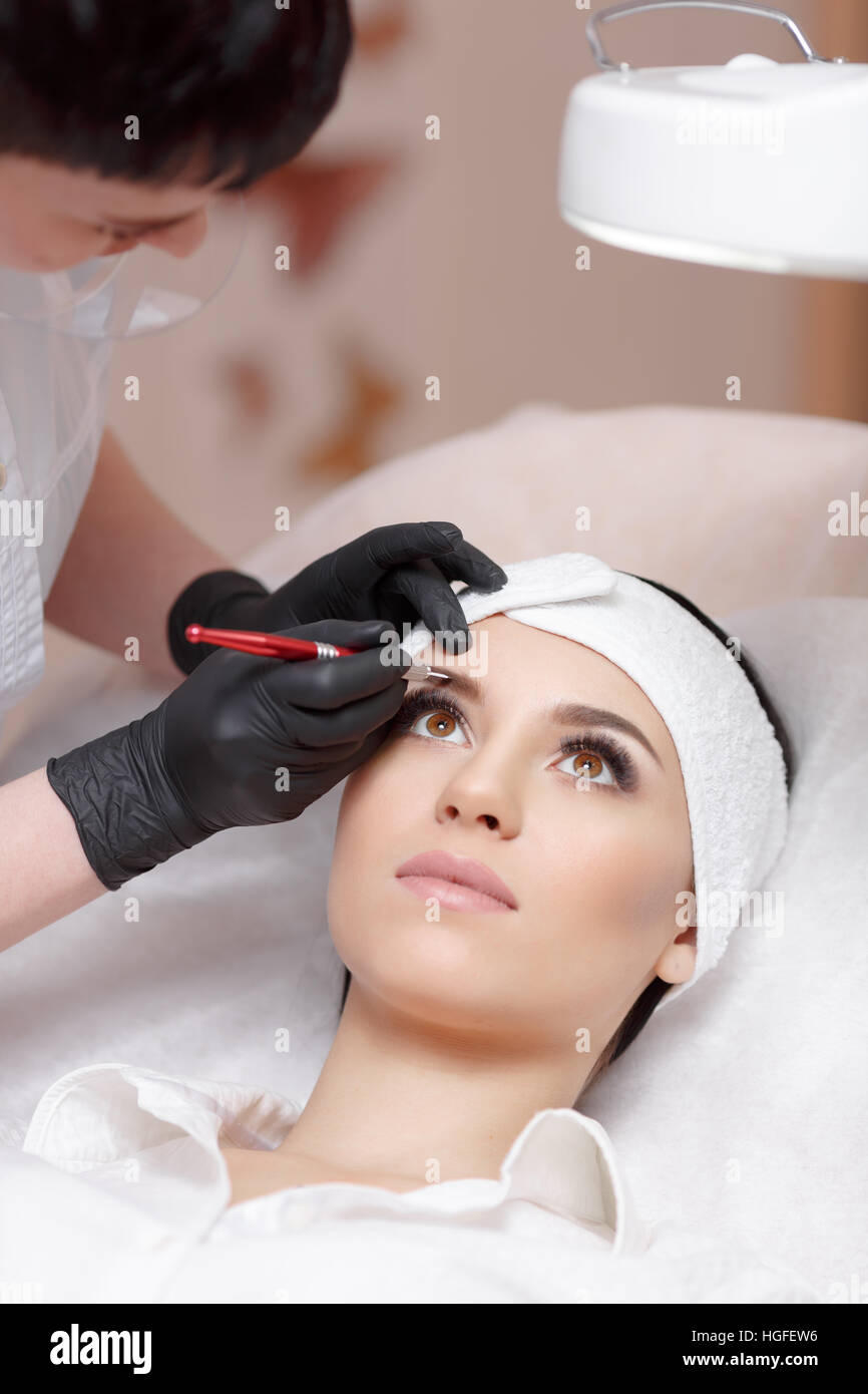 Permanent Make-up-Assistent macht Augenbrauen Korrekturverfahren Stockfoto