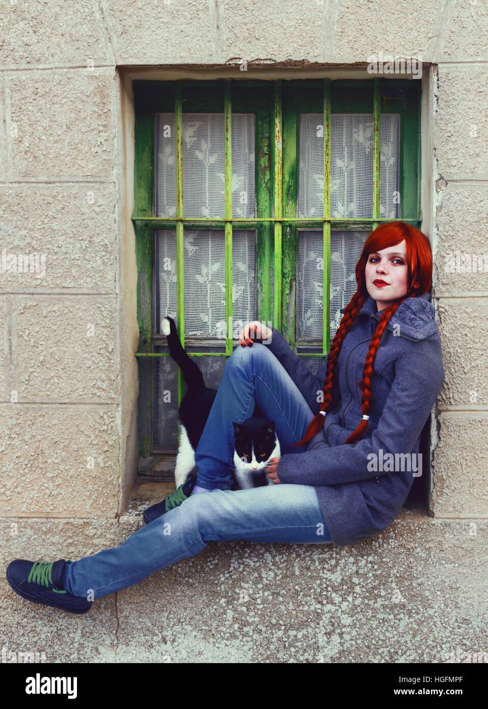 Junge rothaarige Frau, mit zwei langen Zöpfen, sitzen in der Nähe von einem alten Fenster Stockbild