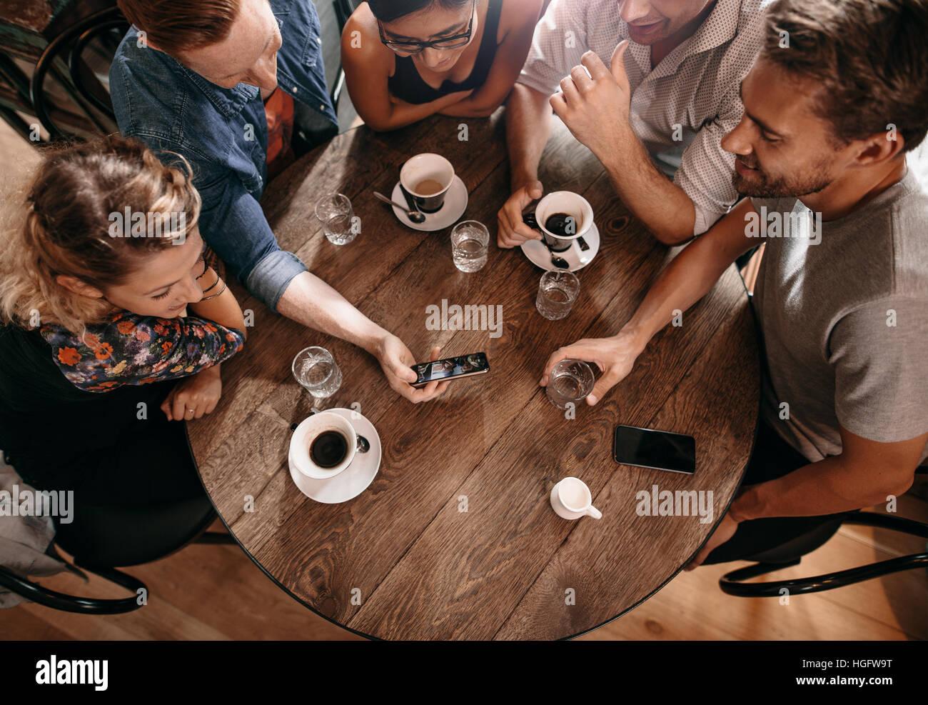 Gruppe von Freunden im Café und Smartphone betrachten. Mann zeigt etwas zu seinen Freunden zu sitzen. Stockbild