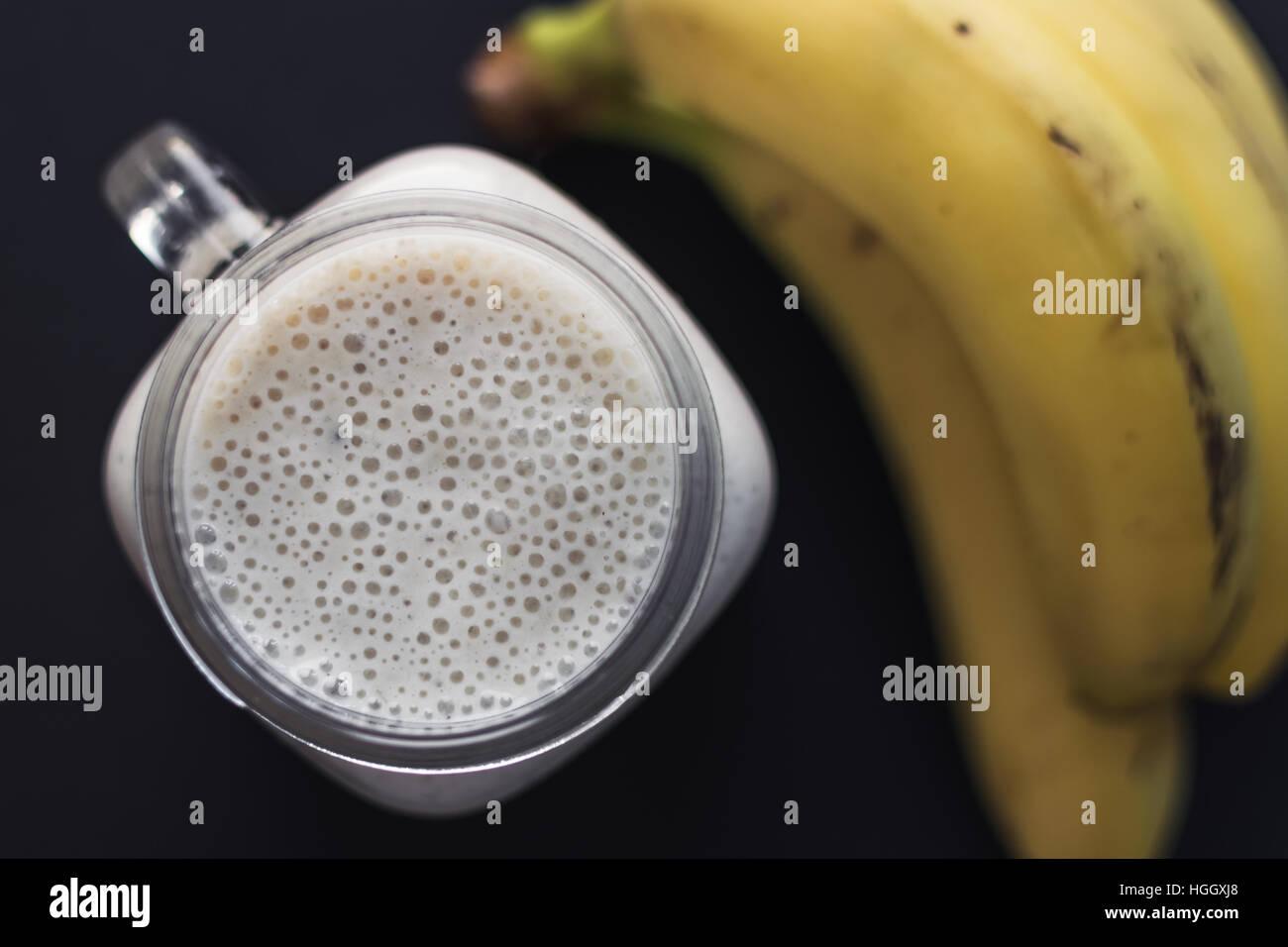 Gesunde Banane und Hafer Smoothie auf schwarzem Hintergrund. Ansicht von oben. Stockbild