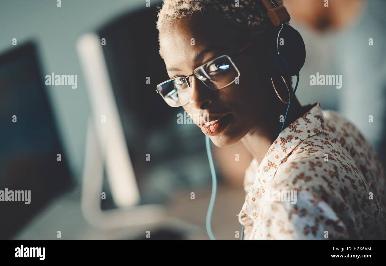 Afroamerikanische Frau mit Brille arbeiten am Schreibtisch im Büro Stockbild