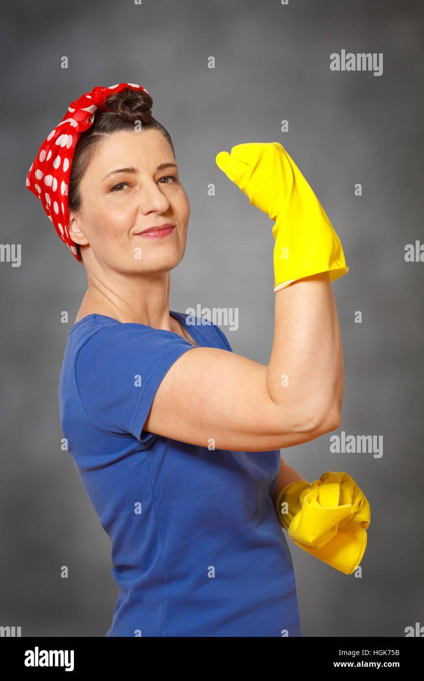 Glücklich Putzfrau mit Kopftuch, gelbe Reinigung Handschuhe und Tuch, zeigen ihre Muskeln, mächtig angibt Stockbild