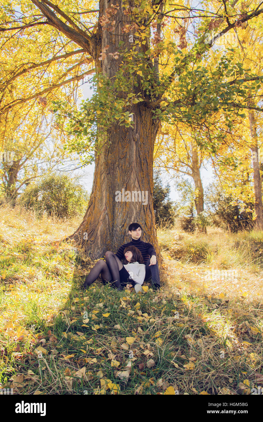Junges Paar in einem Park im Herbst, an einen Baum gelehnt Stockbild