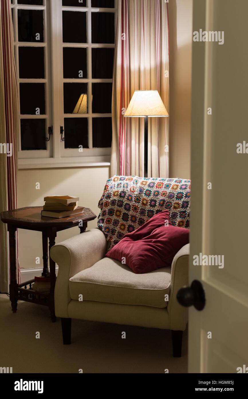 gemütlicher Lesesessel in Haus bei Nacht Stockbild