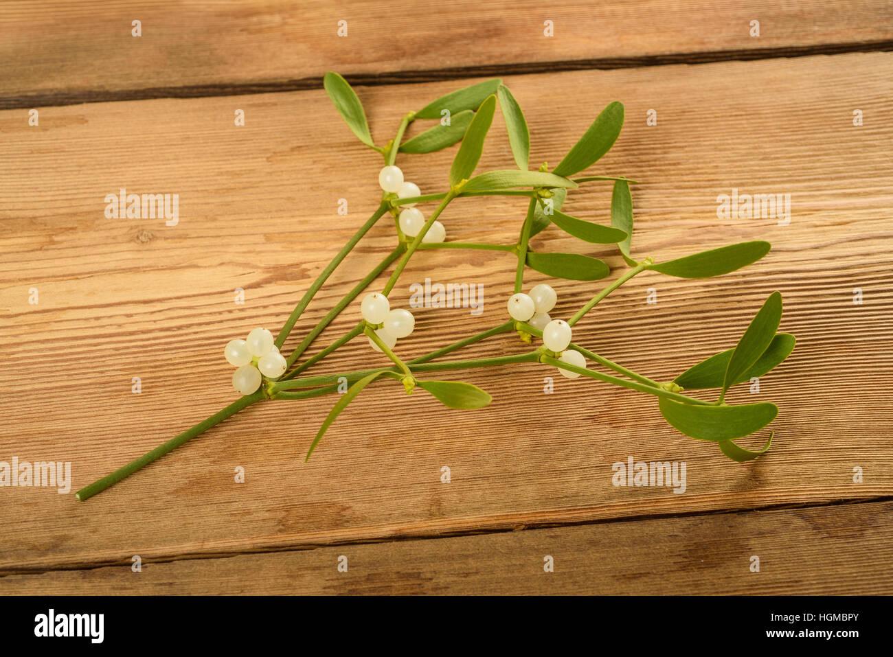 Mistel-Zweig mit Beeren auf Holz Hintergrund Stockbild