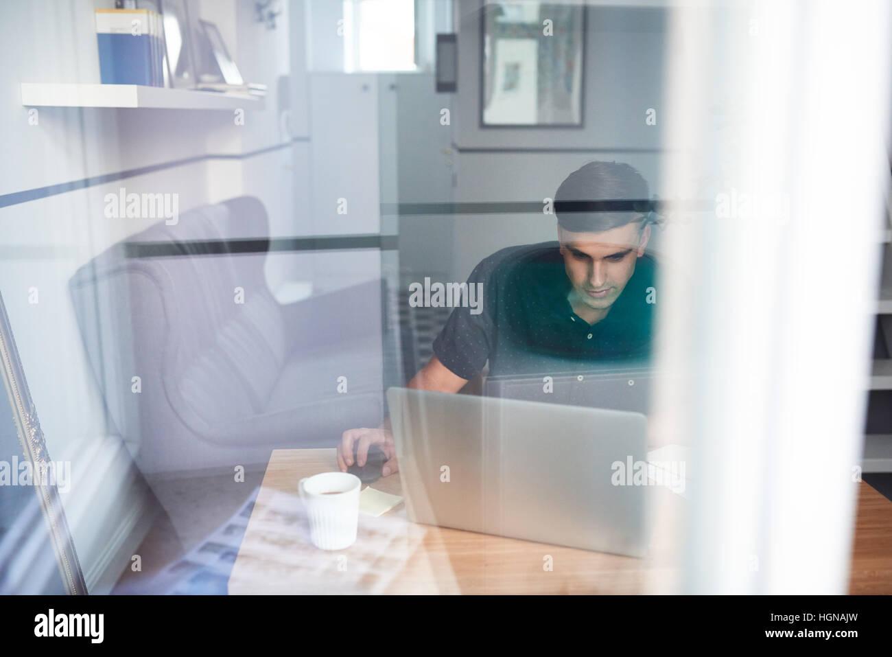 Junger Mann auf einem Laptop zu Hause arbeiten Stockbild