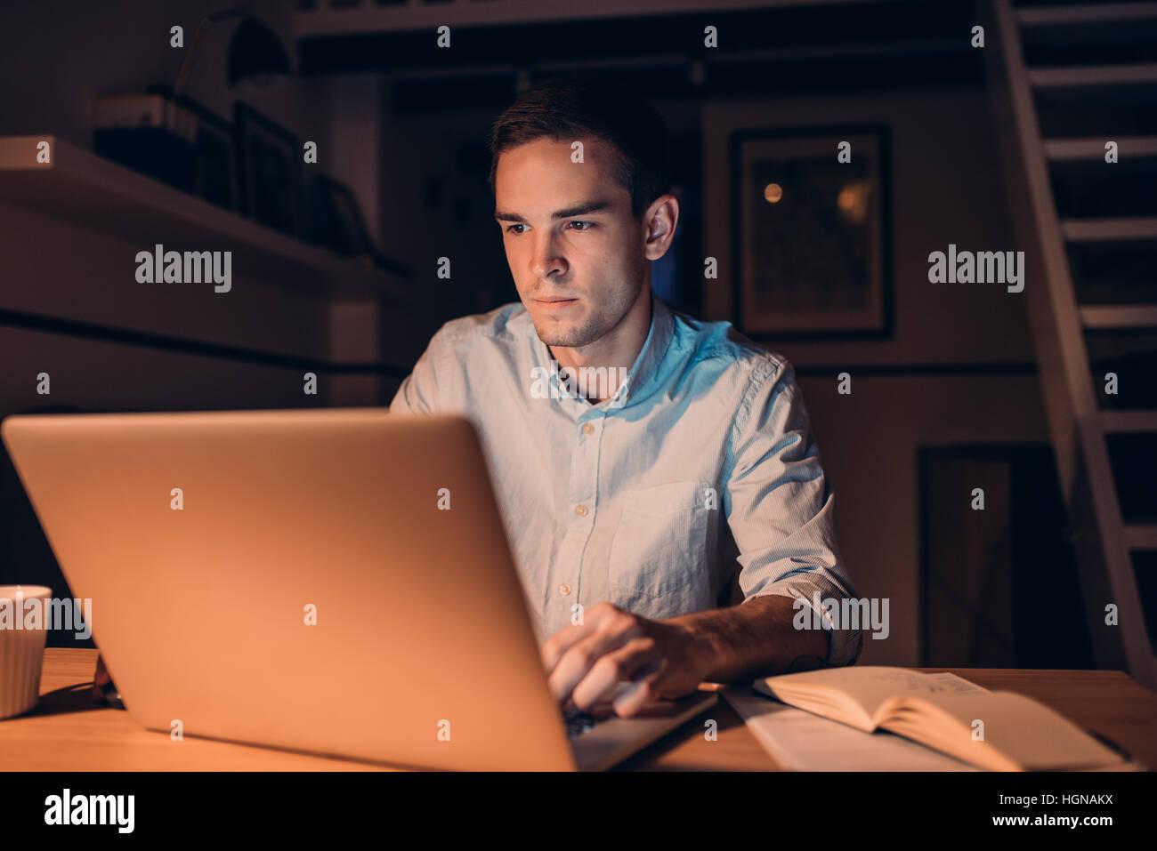 Junger Geschäftsmann auf einem Laptop arbeiten, spät in der Nacht Stockbild