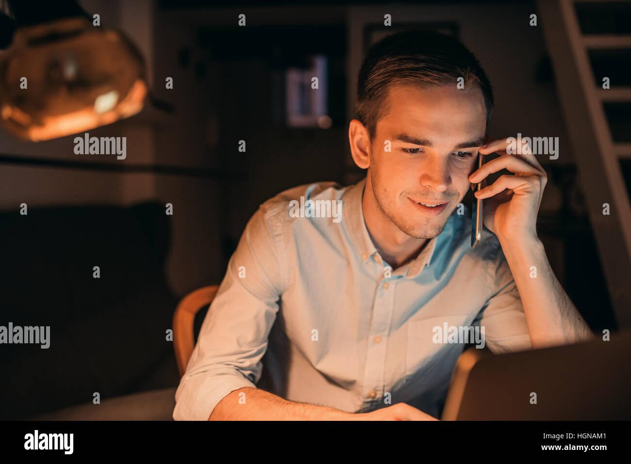 Lächelnde junge Unternehmer bei der Arbeit in den späten Abend Stockbild