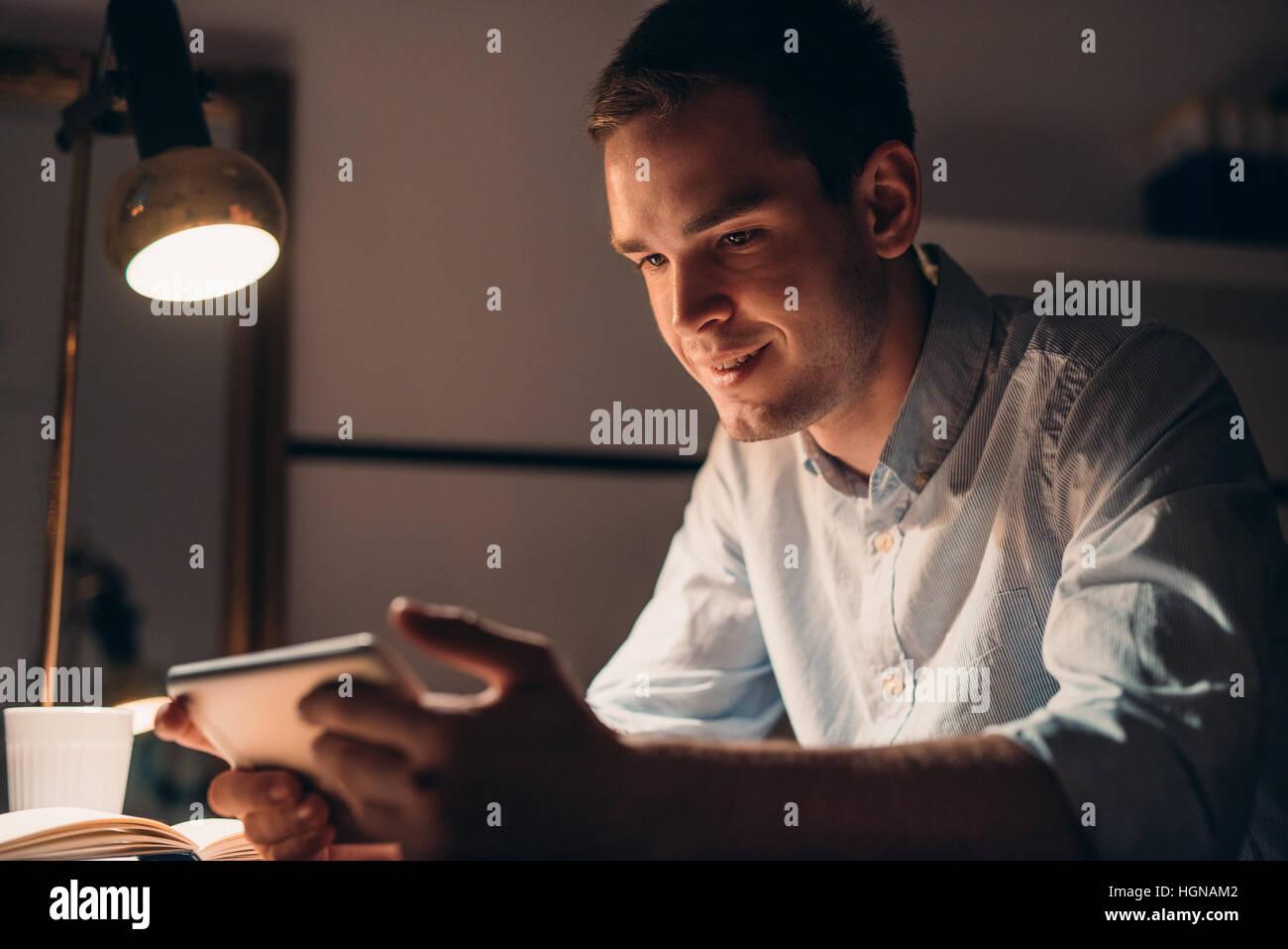 Lächelnde junge Geschäftsmann arbeitet mit einer Tablette spät in die Nacht Stockbild